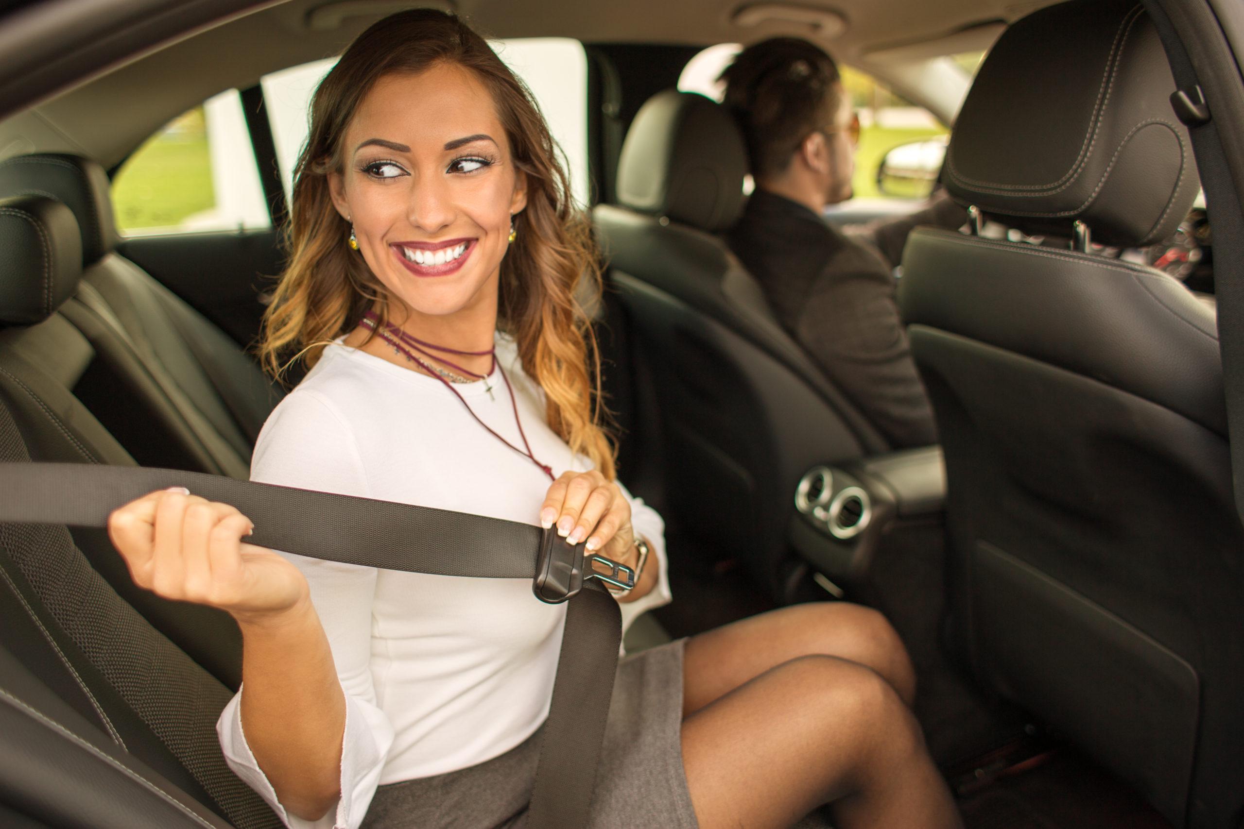 Beautiful businesswoman putting on seatbelt in car